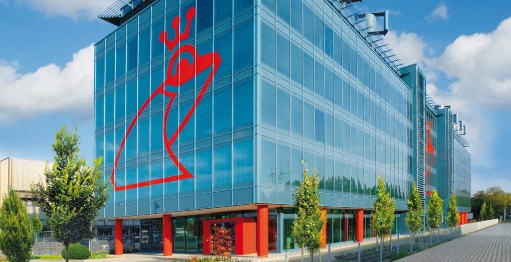 Photo d'un des bâtiments modernes de l'entreprise Werner & Mertz en Allemagne. On peut y voir son logo en forme de grenouille rouge apposé sur les vitres.